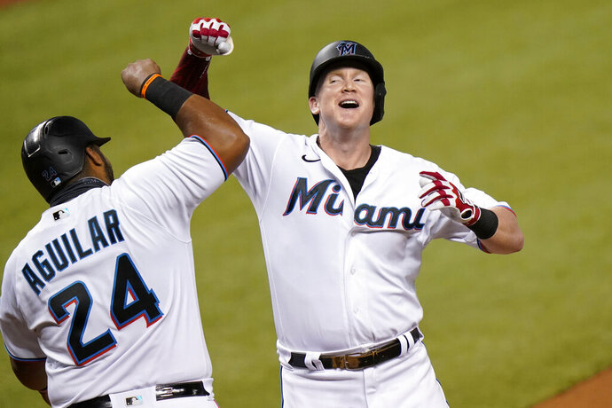 Miami Marlins' Garrett Cooper, right, celebrates with Jesus Aguilar (24) after hitting a two-run home run during the first inning of a baseball game against the Boston Red Sox, Wednesday, Sept. 16, 2020, in Miami. (AP Photo/Lynne Sladky)