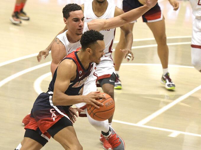 Arizona guard Jemarl Baker Jr. (3) drives around Washington State forward Tony Miller (32) in the first half of an NCAA College Basketball game, Saturday, Jan. 2, 2021, in Pullman, Wash. (AP Photo/Dean Hare)