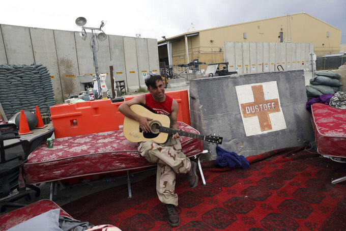 FILE - In this July 5, 202 file photo, an Afghan soldier plays a guitar that was left behind after the American military departed Bagram air base, in Parwan province north of Kabul, Afghanistan. In an interview with The Associated Press Thursday, July 22, 2021, Suhail Shaheen, Afghan Taliban spokesman and a member of the Taliban negotiation team, said the insurgent movement does not want to monopolize power, but there won't be peace until there is a new, negotiated government in Kabul and Afghan President Ashraf Ghani is removed. Shaheen said women will be allowed to work, go to school, and participate in politics but will have to wear the hijab, or headscarf. (AP Photo/Rahmat Gul, File)