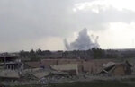 This frame grab from video provided on Tuesday, Feb. 12, 2019, by the Syrian Observatory for Human Rights, an opposition group, that is consistent with independent AP reporting, shows smoke rising from a shell that targeted Islamic State group militants, in the village of Baghouz, Deir El-Zour, eastern Syria. Fighting between U.S.-backed fighters and IS inflicted more casualties among people fleeing the violence in eastern Syria Tuesday where the extremists are on the verge of losing the last area they control. (Syrian Observatory for Human Rights via AP)