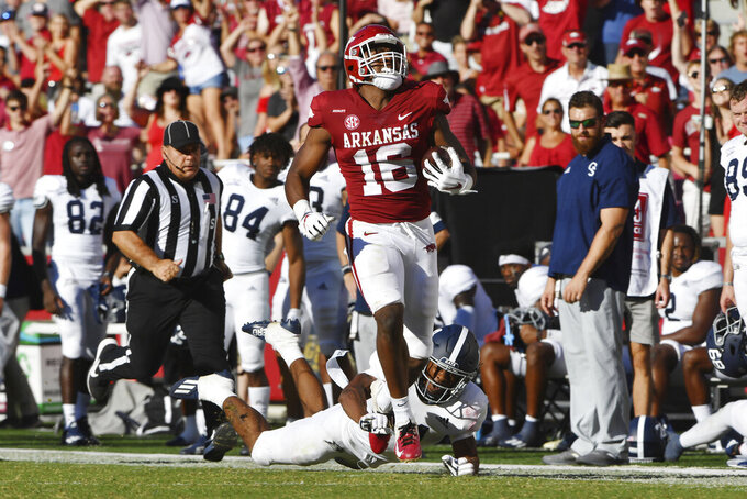 Arkansas receiver Treylon Burks (16) slips past Georgia Southern corner back Darrell Baker Jr. (14) to score a touchdown in the second half of an NCAA college football game Saturday, Sept. 18, 2021, in Fayetteville, Ark. (AP Photo/Michael Woods)