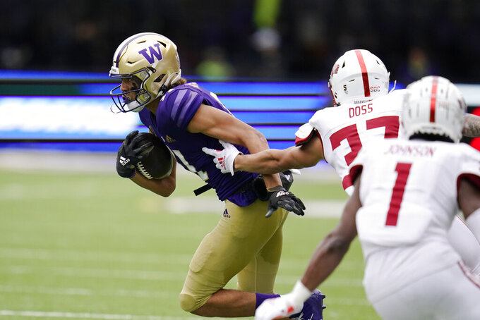 Washington's Jalen McMillan, left, runs with the ball after a reception against Arkansas State in the second half of an NCAA college football game, Saturday, Sept. 18, 2021, in Seattle. (AP Photo/Elaine Thompson)