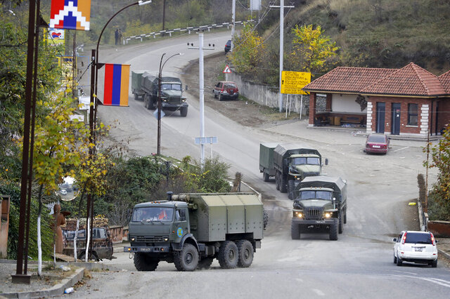 Russian peacekeepers' convoy drive through a street in Stepanakert, the separatist region of Nagorno-Karabakh, on Sunday, Nov. 15, 2020. Ethnic Armenian forces had controlled Nagorno-Karabakh and sizeable adjacent territories since the 1994 end of a separatist war. Fighting resumed in late September and have now ended with an agreement that calls for Azerbaijan to regain control of the outlying territories as well as allowing it to hold on to parts of Nagorno-Karabakh that it seized during the fighting. (AP Photo/Sergei Grits)