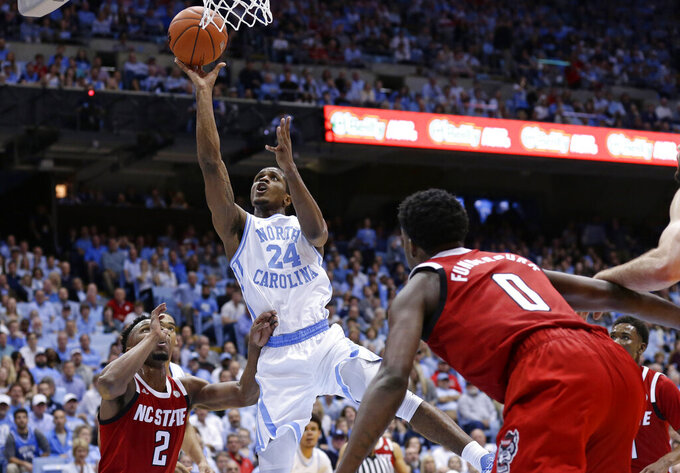 North Carolina's Kenny Williams (24) shoots over North Carolina State's Torin Dorn (2) and DJ Funderburk (0) during the first half of an NCAA college basketball game in Chapel Hill, N.C., Tuesday, Feb. 5, 2019. (AP Photo/Gerry Broome)