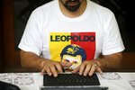 In this Saturday, May 11, 2019 photo, wearing a T-shirt featuring Leopoldo Lopez, Venezuelan opposition leader Freddy Guevara, exiled at the Chilean ambassador's residence, types on a computer keyboard in Caracas, Venezuela. Guevara, in his first televised interview since taking refuge in the lush diplomatic compound 18 months ago, said as foreign embassies in Caracas fill up with dissidents the world will be forced to take notice of how Nicolas Maduro's clinging to power is not only inflicting more damage on what's left of the rule of law in Venezuela but spilling over its borders as well. (AP Photo/Fernando Llano)