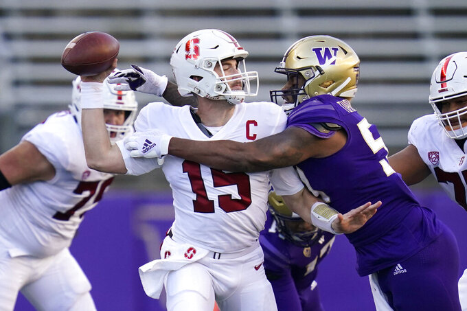Washington linebacker Zion Tupuola-Fetui, right, pressures Stanford quarterback Davis Mills during the second half of an NCAA college football game Saturday, Dec. 5, 2020, in Seattle. (AP Photo/Elaine Thompson)