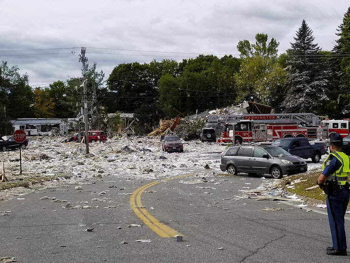 A police officer stands guard, Monday, Sept. 16, 2019, at the scene of a deadly propane explosion which leveled new construction in Farmington, Maine. (Donna Perry/Sun Journal via AP)