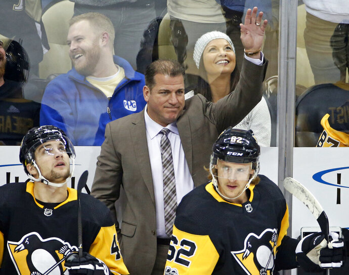 FILE - In this Tuesday, Nov. 14, 2017, file photo, Pittsburgh Penguins assistant coach Mark Recchi acknowledges fans after a video tribute honoring his induction into the Hockey Hall of Fame was played during a timeout in an NHL hockey game between the Pittsburgh Penguins and the Buffalo Sabres in Pittsburgh. The New Jersey Devils have hired Recchi as an assistant coach, the team announced Tuesday, Sept. 8, 2020. Recchi joins new coach Lindy Ruff's staff after three seasons as an assistant with the Pittsburgh Penguins.  (AP Photo/Gene J. Puskar, File)
