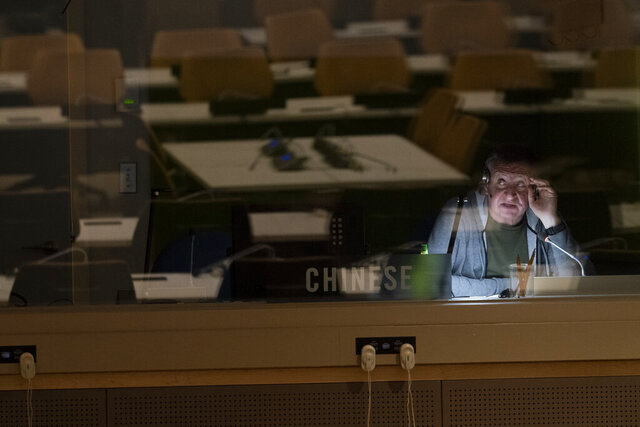 Empty tables in a conference room are seen reflected in a translators booth as he works during the 75th session of the United Nations General Assembly, Wednesday, Sept. 23, 2020, at U.N. headquarters. This year's annual gathering of world leaders at U.N. headquarters will be almost entirely