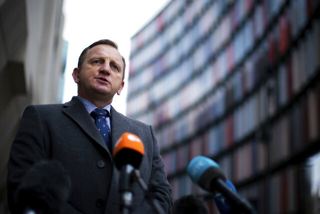 DCI Daniel Stoten gives a statement outside the Old Bailey, where those involved were sentenced for their part in a people-smuggling plot that ended in the deaths of 39 migrants, in London, Friday, Jan. 22, 2021. Four people-smugglers convicted of killing 39 people from Vietnam who died in the back of a container truck as it was shipped to England have been sentenced to between 13 and 27 years in prison. The victims, aged between 15 and 44, were found in October 2019 inside a refrigerated container that had traveled by ferry from Belgium to the eastern England port of Purfleet. (Aaron Chown/PA via AP)