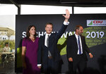 Governor of Saxony Michael Kretschmer, center, waves to supporters beside his partner Annett Hofmann, left, at an election party in Dresden, Germany, Sunday, Sept. 1, 2019. The citizens of the German states Saxony and Brandenburg elected their new parliament. (Robert Michael/dpa via AP)