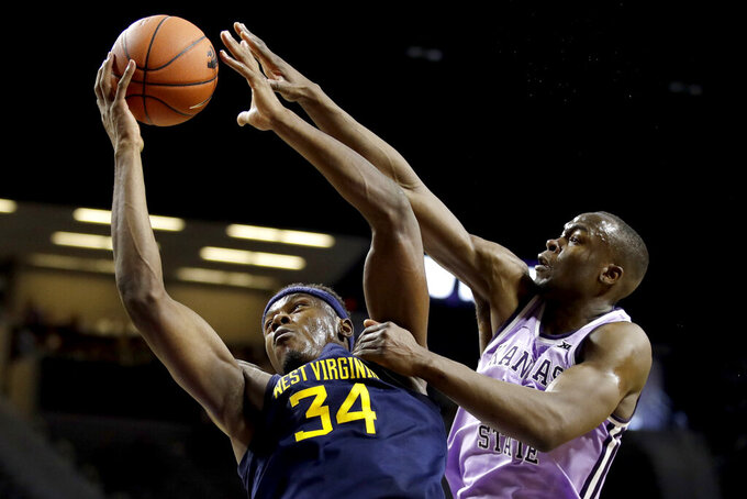 West Virginia's Oscar Tshiebwe (34) shoots under pressure from Kansas State's Makol Mawien during the first half of an NCAA college basketball game Saturday, Jan. 18, 2020, in Lawrence, Kan. (AP Photo/Charlie Riedel)