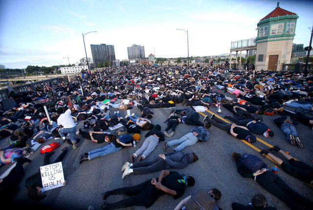 Marchers lay down on the Burnside Bridge for nine minutes on Tuesday evening, June 2, 2020, symbolizing the amount of time a Minneapolis police officer knelt on George Floyd's neck. Floyd died after being restrained by Minneapolis police officers on May 25. (Sean Meagher/The Oregonian via AP)