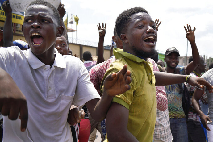 Supporters of spurned Congo opposition candidate Martin Fayulu react at the presidential elections results just before Fayuly arrived to address them in Kinshasha, Congo, Friday, Jan. 11, 2019. Hundreds gathered to denounce what they called