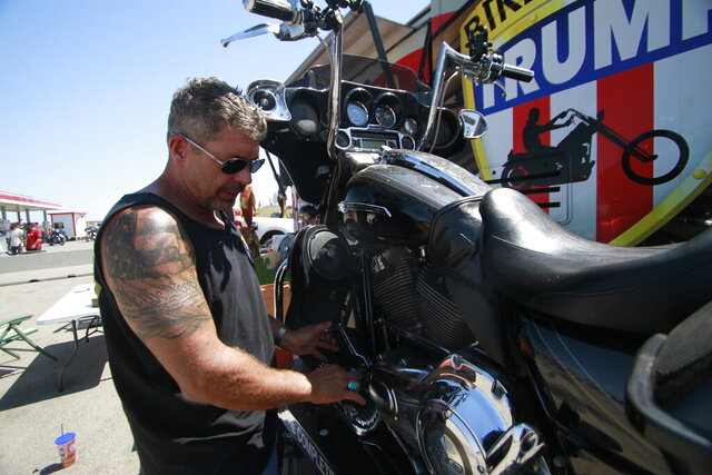 Chris Cox, the founder of Bikers for Trump, examines his motorcycle on Saturday, Aug. 8, 2020, outside the Bikers for Trump trailer he brought to the Sturgis Motorcycle Rally, in Sturgis, S.D.  The group has taken advantage of recent motorcycle rallies, which have been some of the largest mass gatherings in the country, to make direct appeals to register to vote. While the group has gained a significant online following for its shows of bravado, it remains to be seen if they can get ballot boxes filled with bikers, many who hail from the suburbs. (AP Photo/Stephen Groves)