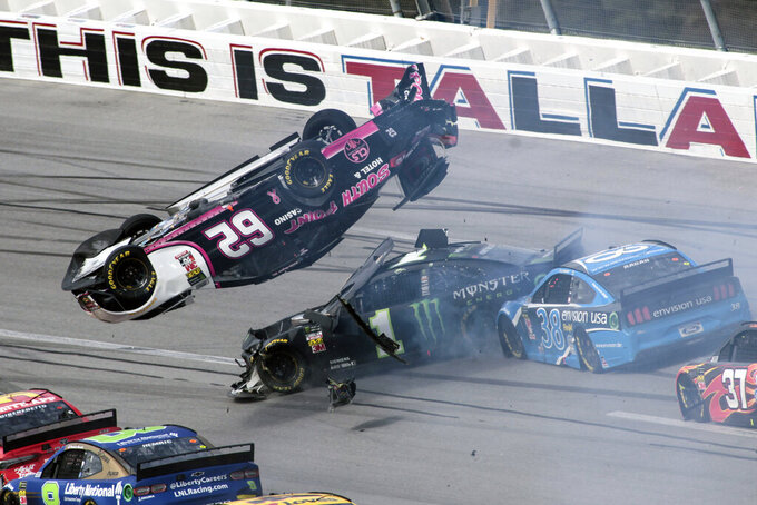Brendan Gaughan (62) flips in Turn 3 as driver Kurt Busch (1) and David Ragan (38) pass underneath during a NASCAR Cup Series auto race at Talladega Superspeedway, Monday, Oct 14, 2019, in Talladega, Ala. (AP Photo/Greg McWilliams)