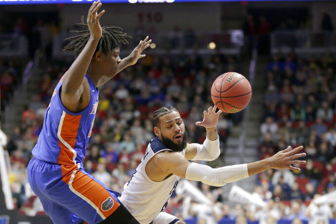 Nevada's Cody Martin, right, loses control of the ball as he drives around Florida's Andrew Fava, left, during the first half of a first round men's college basketball game in the NCAA Tournament in Des Moines, Iowa, Thursday, March 21, 2019. (AP Photo/Nati Harnik)