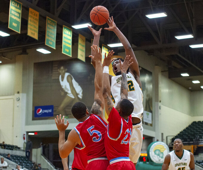 Norfolk State forward Alex Long drives in for a layup against two Delaware State defenders during the first half of an NCAA college basketball game, Saturday, Jan. 5, 2019, in Norfolk, Va. (Mike Caudill/The Virginian-Pilot via AP)