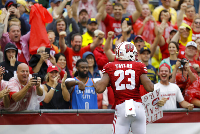 Taylor helps No. 13 Wisconsin trounce No. 11 Michigan 35-14