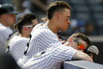 New York Yankees' DJ LeMahieu, right, leans his head on the dugout railing during the ninth inning of a baseball game against the Colorado Rockies at Yankee Stadium, Sunday, July 21, 2019, in New York. (AP Photo/Seth Wenig)