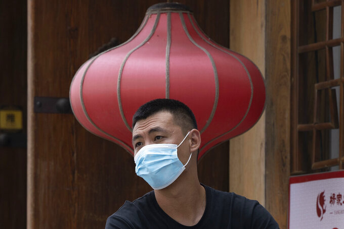 A man wearing a mask to curb the spread of the coronavirus sits near a red lantern outside a restaurant in Beijing Monday, July 13, 2020. China reported eight new cases, all of them brought from outside the country, as domestic community infections fall to near zero. (AP Photo/Ng Han Guan)