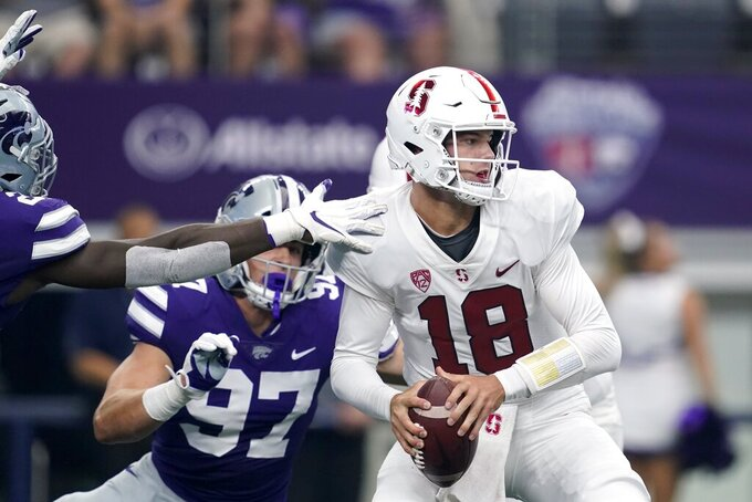 Stanford quarterback Tanner McKee (18) is pressured by Stanford defensive end Aaron Armitage (97) and others as he prepares to throw a pass in the first half of an NCAA college football game in Arlington, Texas, Saturday, Sept. 4, 2021. (AP Photo/Tony Gutierrez)