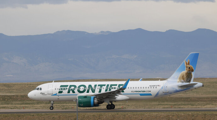 In this April 23, 2020 photo a Frontier Airlines jetliner taxis to a runway for take off from Denver International Airport in Denver. Lawmakers on Capitol Hill lashed out Wednesday, May 6, 2020 against Frontier Airlines over the budget carrier's move to charge passengers extra to guarantee they will sit next to an empty middle seat while flying during the coronavirus outbreak. (AP Photo/David Zalubowski)