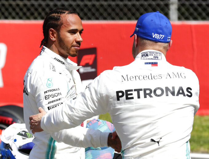 Mercedes driver Lewis Hamilton of Britain, left congratulates with his teammate driver Valtteri Bottas of Finland, after the qualifying session at the Barcelona Catalunya racetrack in Montmelo, just outside Barcelona, Spain, Saturday, May 11, 2019. The Formula One race will take place on Sunday. Bottas will start from the pole position. (AP Photo/Manu Fernandez)