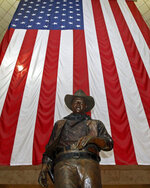 FILE - In this Sept. 11, 2011, file photo, a bronze statue of late actor John Wayne stands before a four-story high United States flag at John Wayne Orange County Airport in Santa Ana, Calif. In the latest move to change place names in light of U.S. racial history, leaders of Orange County's Democratic Party are pushing to drop film legend Wayne's name, statue and other likenesses from the county's airport because of his racist and bigoted comments. (AP Photo/Reed Saxon, File)