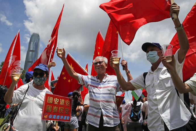 Pro-China supporters holding Chinese national flags, toast during a rally to celebrate the approval of a national security law for Hong Kong, in Hong Kong, Tuesday, June 30, 2020. Hong Kong media are reporting that China has approved a contentious law that would allow authorities to crack down on subversive and secessionist activity in Hong Kong, sparking fears that it would be used to curb opposition voices in the semi-autonomous territory. A placard reads