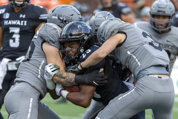 Hawaii wide receiver Jared Smart (23) is gang tackled by a host of Air Force defenders during the first half of an NCAA college football game against Air Force, Saturday, Oct. 19, 2019, in Honolulu. (AP Photo/Eugene Tanner)