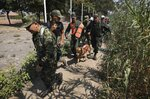 Colombian soldiers escort two Venezuelan National Guardsmen who deserted their post near the Simon Bolivar International Bridge, in La Parada, Colombia, Monday, Feb. 25, 2019. (AP Photo/Fernando Vergara)