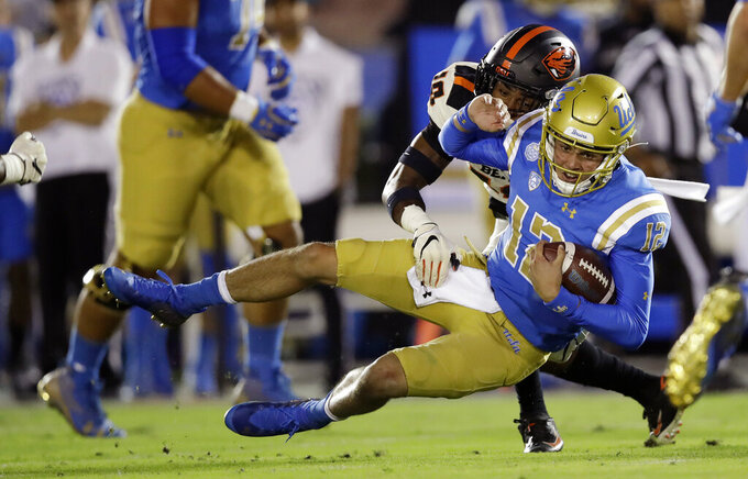 UCLA quarterback Austin Burton (12) is tackled y Oregon State defensive back Omar Hicks-Onu, top, during the first half of an NCAA college football game Saturday, Oct. 5, 2019, in Pasadena, Calif. (AP Photo/Marcio Jose Sanchez)