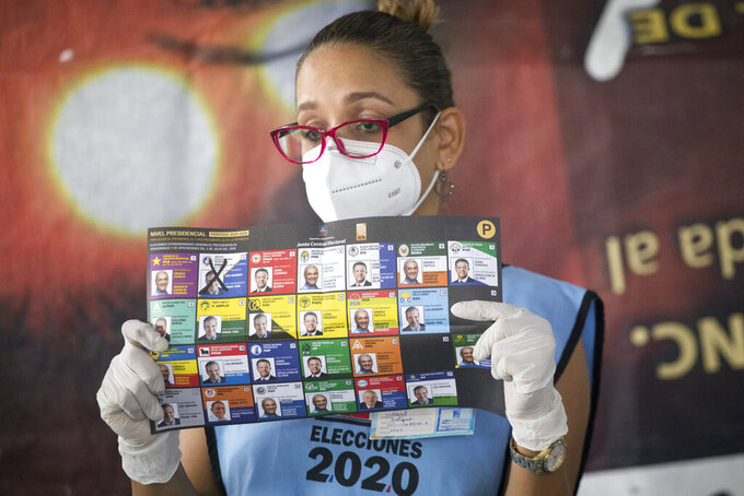 An electoral official wears a protective mask as a precaution against the spread of the new coronavirus, while counting ballots after polls closed during the presidential elections, in Santo Domingo, Dominican Republic, Sunday, July 5, 2020. (AP Photo/Tatiana Fernandez)
