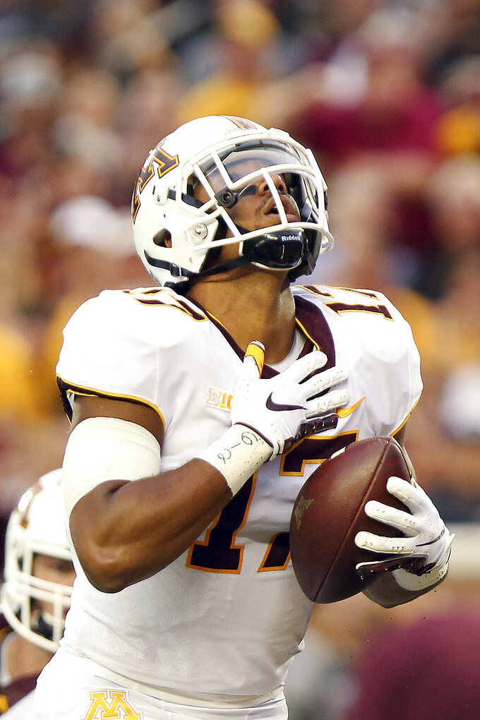 FILE - In this Aug. 30, 2018, file photo, Minnesota tight end Seth Green (17) reacts to scoring a touchdown against New Mexico State during an NCAA college football game, in Minneapolis. Green was going to be the third-string quarterback for Minnesota this season, until the Gophers coaches got the idea to better apply his skills. Now he's a hybrid who also plays wide receiver and tight end, plus a ball-carrying role that produced two touchdowns off a direct snap in the opening win against New Mexico State. Green and the Gophers will face a much tougher test, particularly on defense, when Fresno State visits this weekend. (AP Photo/Stacy Bengs, File)