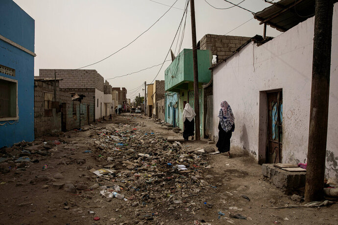 In this July 20, 2019 photo, Ethiopian migrant women walk through the Basateen area of Aden, Yemen. Many migrants languish for months in the slums of Basateen, a district that was once a green area of gardens but now is covered in decrepit shacks of cinder blocks, concrete, tin and tarps, amid open sewers. (AP Photo/Nariman El-Mofty)