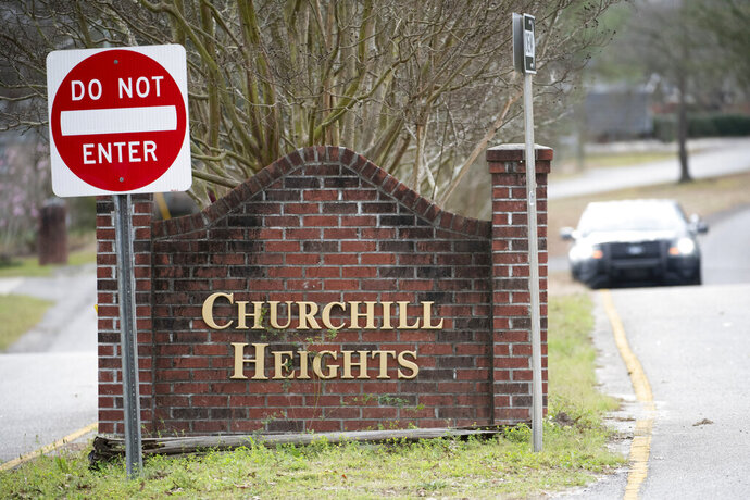 A police officer blocks a road near an entrance to the Churchill Heights neighborhood Thursday, Feb. 13, 2020, in Cayce, S.C., where 6-year-old Faye Marie Swetlik recently went missing just after getting off a school bus. Hundreds of officers in Cayce, along with state police and FBI agents, are working around the clock to try to find Swetlik, who was last seen Monday, Cayce Public Safety Officer Sgt. Evan Antley reiterated Thursday. (AP Photo/Sean Rayford)