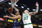 Indiana Pacers guard Malcolm Brogdon (7) is fouled by Boston Celtics forward Daniel Theis (27) as he shoots during the first half of an NBA basketball game in Indianapolis, Wednesday, Dec. 11, 2019. (AP Photo/Michael Conroy)