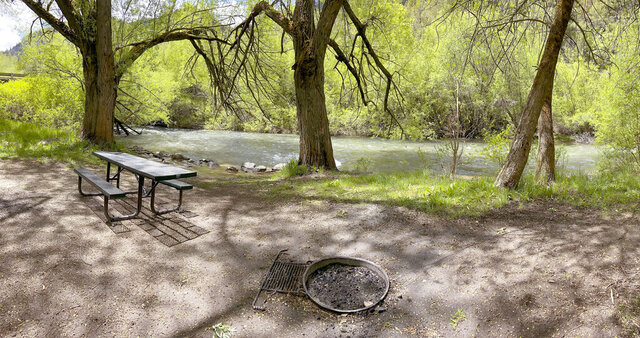 In this Thursday, May 21, 2020, photo, a campsite at Wood Camp sits along the Logan River, near Logan, Utah. With outdoor recreation being one of the few activities available during the COVID-19 pandemic, campsites are undergoing a large uptick in positive and negative use. Local forest rangers are encouraging folks to treat campgrounds respectfully, extinguish campfires and plan ahead for trips. (Eli Lucero/The Herald Journal via AP)