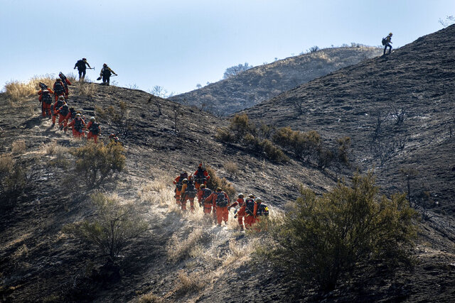 Hand crews climb rugged terrain along Agua Dulce Canyon road Monday, July 6, 2020, in Agua Dulce, Calf. The Soledad fire which broke out Sunday afternoon has scorched 1300 acres and is now 30% contained as firefighters and hand crews work through high temperatures to make sure the flames are contained. (David Crane/The Orange County Register via AP)