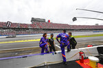 Crew members for the car driven by Denny Hamlin wait around in the pit area as a truck driess the track before a delayed NASCAR Cup series auto race Sunday, Oct. 3, 2021, in Talladega, Ala. (AP Photo/John Amis)