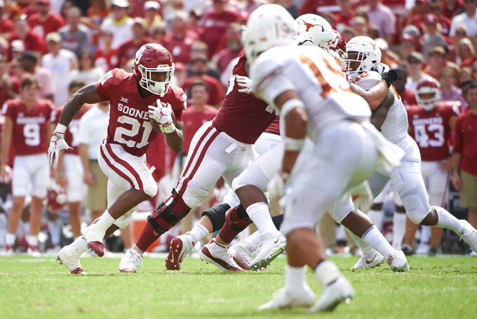 Oklahoma running back Marcelias Sutton (21) breaks free against Texas during the second half of an NCAA college football game at the Cotton Bowl, Saturday, Oct. 6, 2018, in Dallas. (AP Photo/Cooper Neill)
