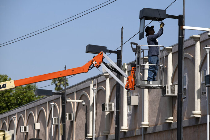 A worker fixes a street lamp in the Van Nuys section of Los Angeles on Thursday, June 17, 2021. California's power grid operator called for voluntary energy conservation Thursday as much of the state sweltered under a heat wave that has baked the U.S. West. (AP Photo/Richard Vogel)