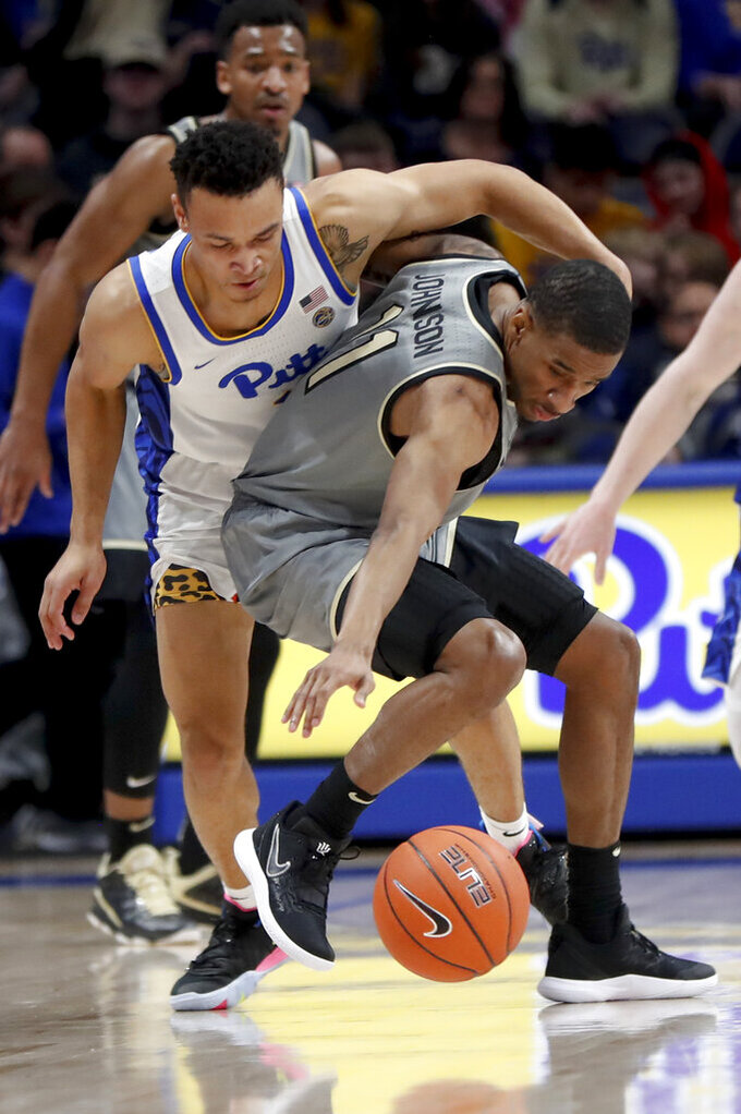 Pittsburgh's Trey McGowens, left, and Wake Forest's Torry Johnson (11) battle for a loose ball during the first half of an NCAA college basketball game, Saturday, Jan. 4, 2020, in Pittsburgh. (AP Photo/Keith Srakocic)