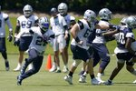 Dallas Cowboys running back Ezekiel Elliott (21) carries the ball during a workout at the team's NFL football training facility in Frisco, Texas, Wednesday, Aug. 25, 2021. (AP Photo/Tony Gutierrez)