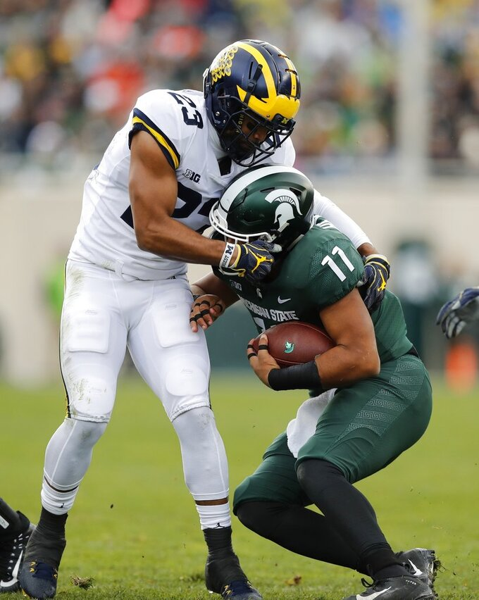 Michigan defensive back Tyree Kinnel (23) stops Michigan State running back Connor Heyward (11) during the first half of an NCAA college football game, Saturday, Oct. 20, 2018, in East Lansing, Mich. (AP Photo/Carlos Osorio)