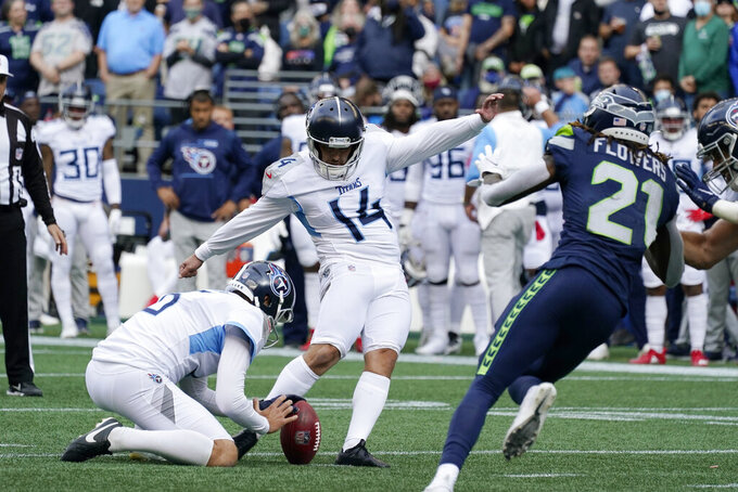 Tennessee Titans kicker Randy Bullock (14) kicks a field goal as Brett Kern holds during the first half of an NFL football game against the Seattle Seahawks, Sunday, Sept. 19, 2021, in Seattle. (AP Photo/Elaine Thompson)