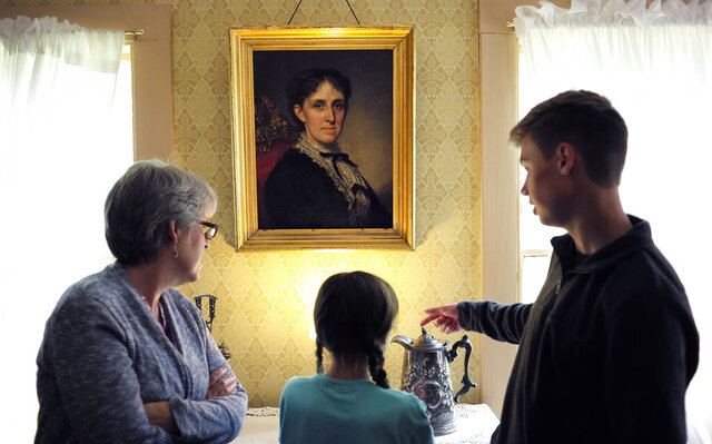 FILE - In this May 17, 2018 file photo, museum visitors stand near a portrait of author Louisa May Alcott by American artist George Healy at Orchard House in Concord, Mass. The current issue of The Strand Magazine will give readers the chance to discover an obscure and unfinished work of fiction by Alcott,