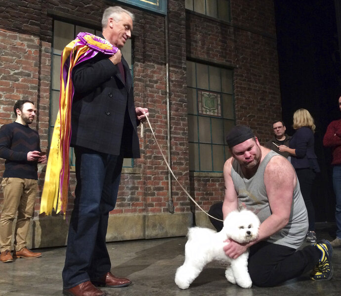 Westminster dog show winner Flynn the bichon frise poses with handler Bill McFadden foreground left, and actor Daniel Stewart Sherman, before doing a walk-on part at the Broadway musical