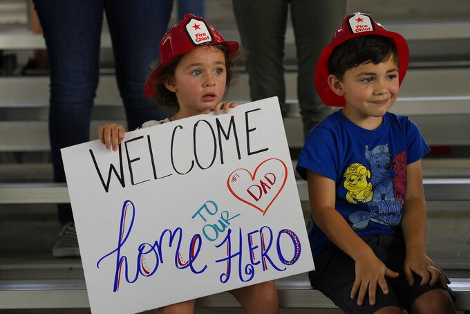 Isabella, 3, and Eric, 4, wait to welcome home their father, Capt. Eric Hernandez, as members of Miami-Dade Fire Rescue's urban search and rescue team are reunited with their families after weeks of working on the rubble pile at the collapsed Champlain Towers South condominium, on Friday, July 23, 2021, in Doral, Fla. (AP Photo/Rebecca Blackwell)